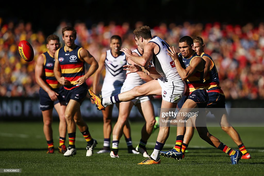 Michael Barlow of the Dockers kicks the ball while under pressure from Charlie Cameron of the Crows during the round six AFL match between the Adelaide Crows and the Fremantle Dockers at Adelaide Oval on April 30, 2016 in Adelaide, Australia.