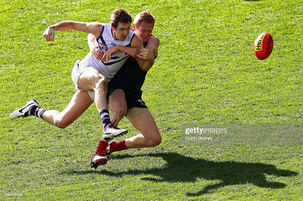 Michael Barlow of the Dockers kicks whilst being tackled by Jordie McKenzie of the Demons during the round 21 AFL match between the Melbourne Demons and the Fremantle Dockers at Melbourne Cricket Ground on August 18, 2013 in Melbourne, Australia.