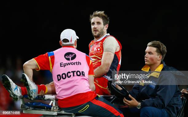 Michael Barlow of the suns suffers an injury during the round 13 AFL match between the Gold Coast Suns and the Carlton Blues at Metricon Stadium on...