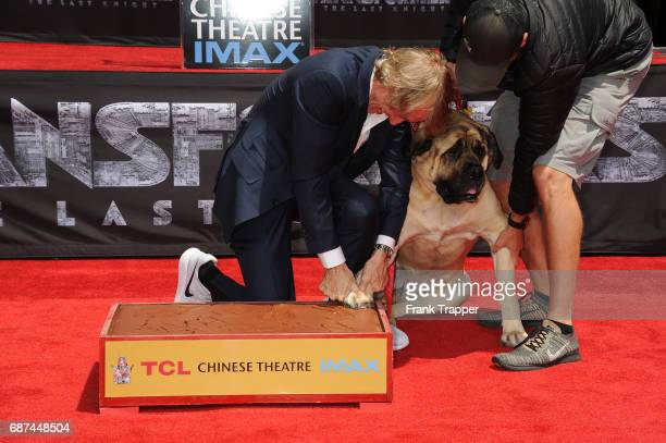Michael Bay and his dog Rebel pose during the Hand and Footprint Ceremony at TCL Chinese Theatre IMAX on May 23 2017 in Hollywood California