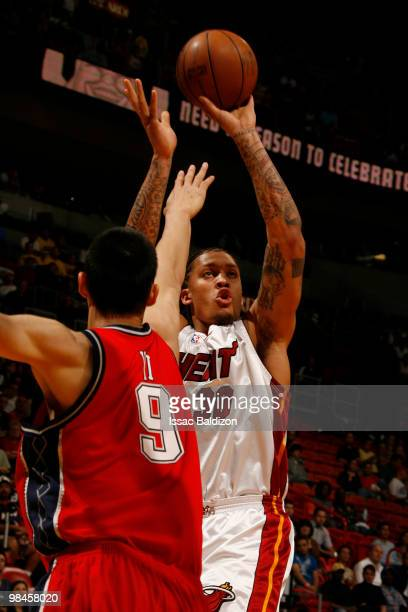 Michael Beasley of the Miami Heat shoots against Yi Jianlian of the New Jersey Nets on April 14 2010 at American Airlines Arena in Miami Florida NOTE...