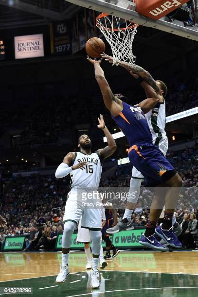 Michael Beasley of the Milwaukee Bucks blocks a shot by Alan Williams of the Phoenix Suns during the first half of a game at the BMO Harris Bradley...