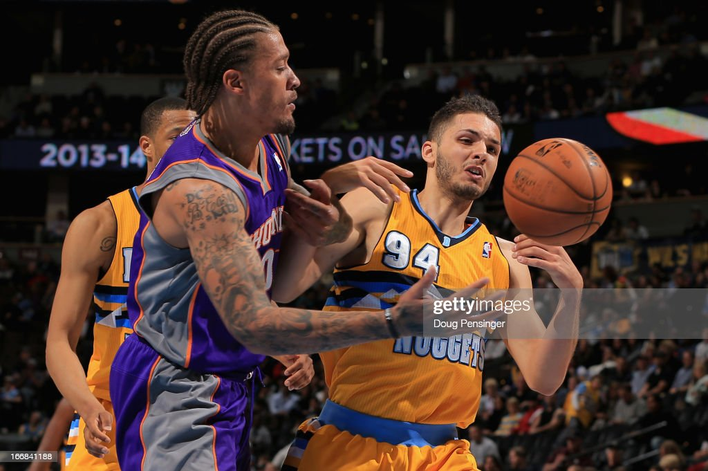 Michael Beasley #0 of the Phoenix Suns and Evan Fournier #94 of the Denver Nuggets battle for control of a loose ball at the Pepsi Center on April 17, 2013 in Denver, Colorado. The Nuggets defeated the Suns 118-98.