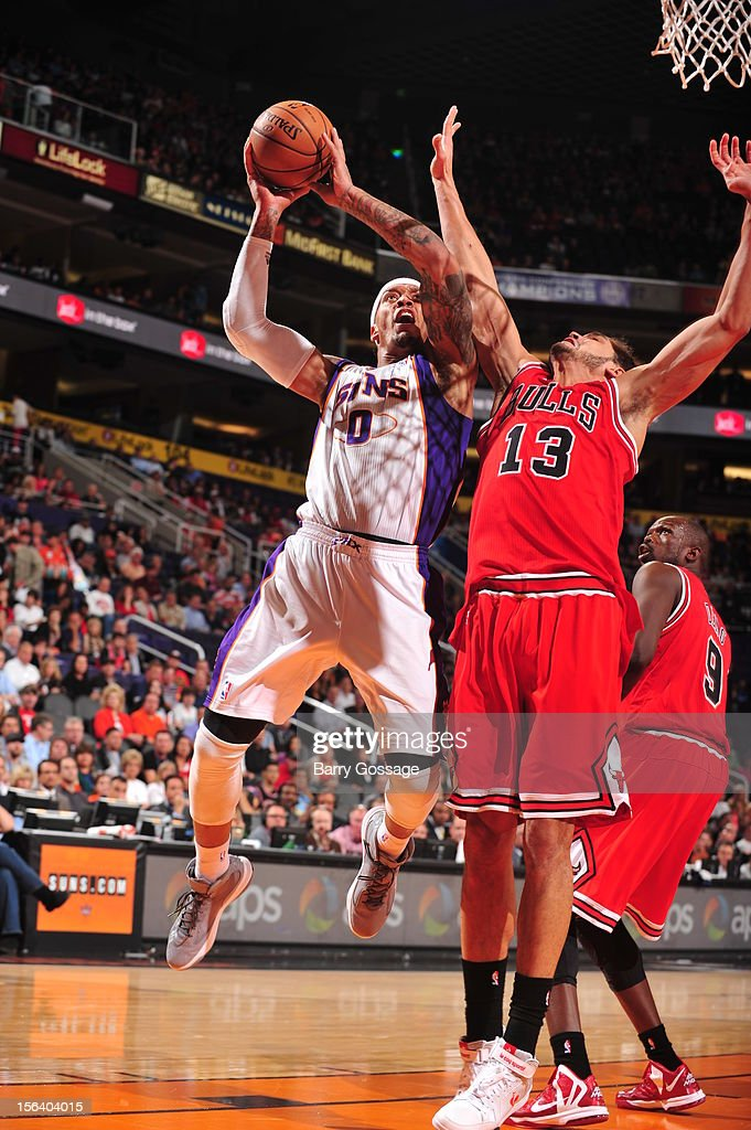 Michael Beasley #0 of the Phoenix Suns drives for a shot against Joakim Noah #13 of the Chicago Bulls on November 14, 2012 at U.S. Airways Center in Phoenix, Arizona.