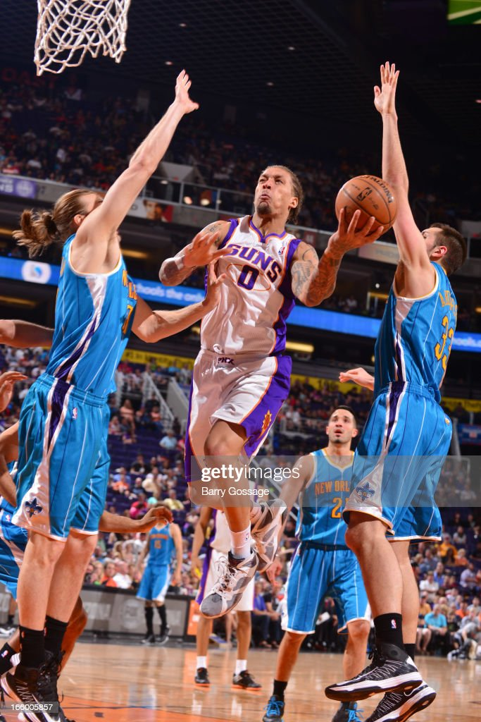 Michael Beasley #0 of the Phoenix Suns drives to the basket against Lou Amundson #17 and Ryan Anderson #33 of the New Orleans Hornets on April 7, 2013 at U.S. Airways Center in Phoenix, Arizona.
