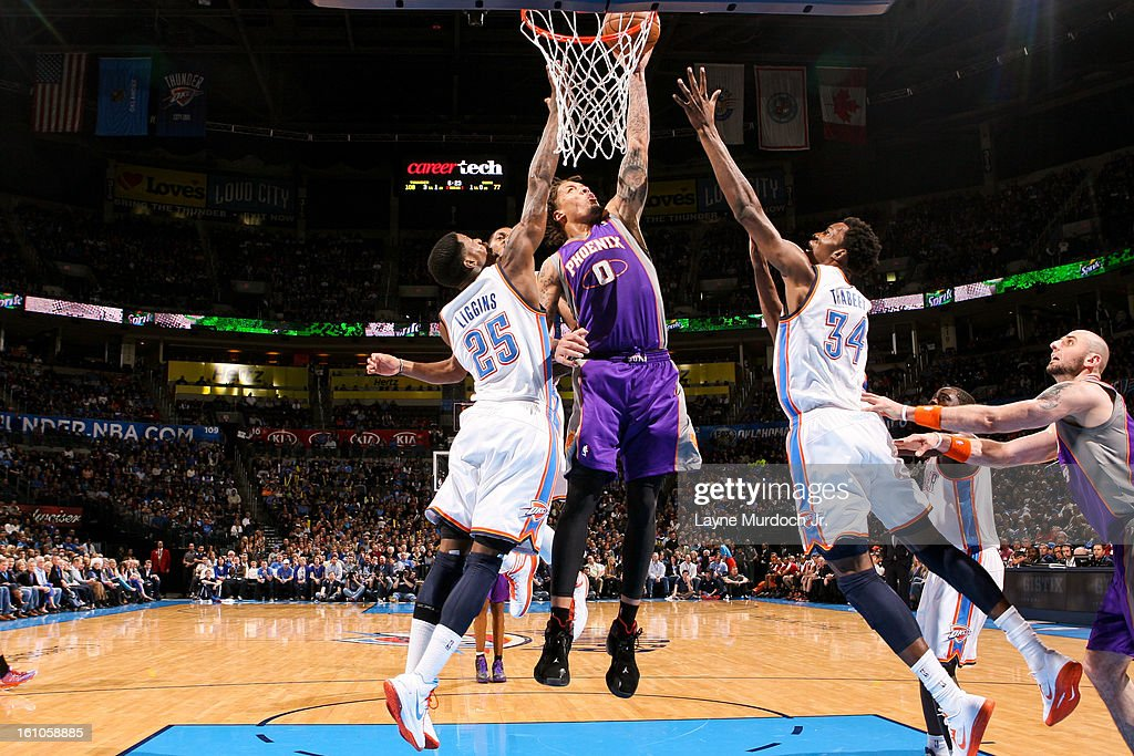 Michael Beasley #0 of the Phoenix Suns drives to the basket against DeAndre Liggins #25 and Hasheem Thabeet #34 of the Oklahoma City Thunder on February 8, 2013 at the Chesapeake Energy Arena in Oklahoma City, Oklahoma.