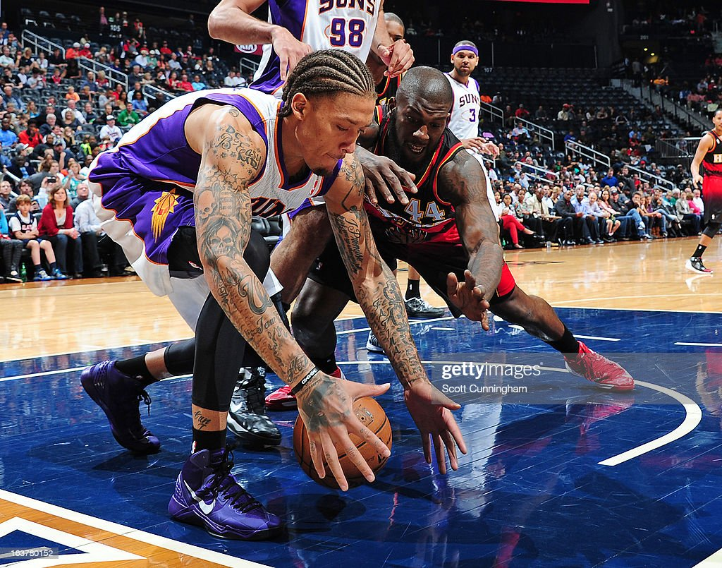 Michael Beasley #0 of the Phoenix Suns fights for the ball against Ivan Johnson #44 of the Atlanta Hawks on March 15, 2013 at Philips Arena in Atlanta, Georgia.
