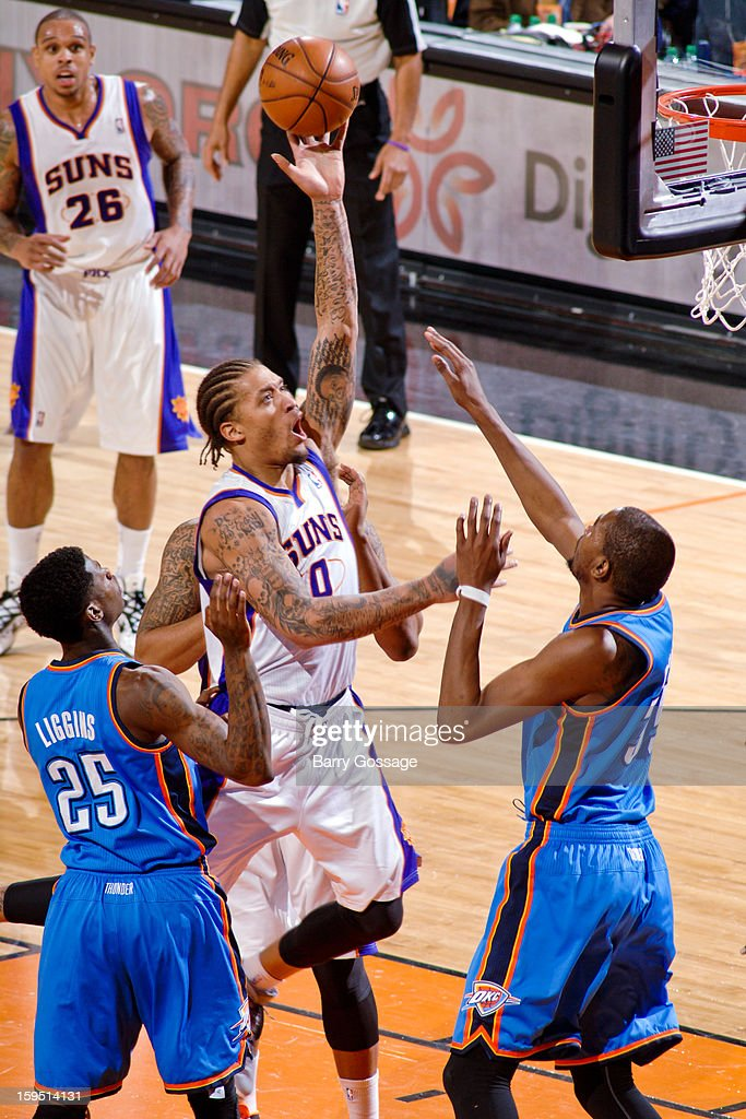 Michael Beasley #0 of the Phoenix Suns shoots in the lane against DeAndre Liggins #25 and Kevin Durant #35 of the Oklahoma City Thunder on January 14, 2013 at U.S. Airways Center in Phoenix, Arizona.