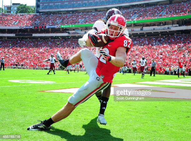 Michael Bennett of the Georgia Bulldogs makes a catch for a second quarter touchdown against Ethan Davis of the Troy Trojans at Sanford Stadium on...
