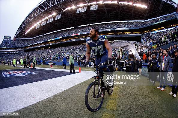 Michael Bennett of the Seattle Seahawks rides a police bike after the Seahawks 2822 overtime victory against the Green Bay Packers during the 2015...