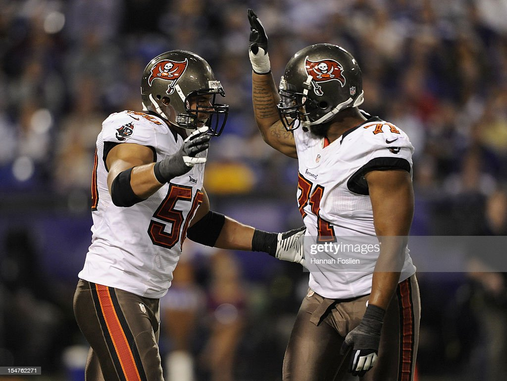 Michael Bennett #71 of the Tampa Bay Buccaneers congratulates Daniel Te'o-Nesheim #50 on a sack during the second quarter on October 25, 2012 at Mall of America Field at the Hubert H. Humphrey Metrodome in Minneapolis, Minnesota.