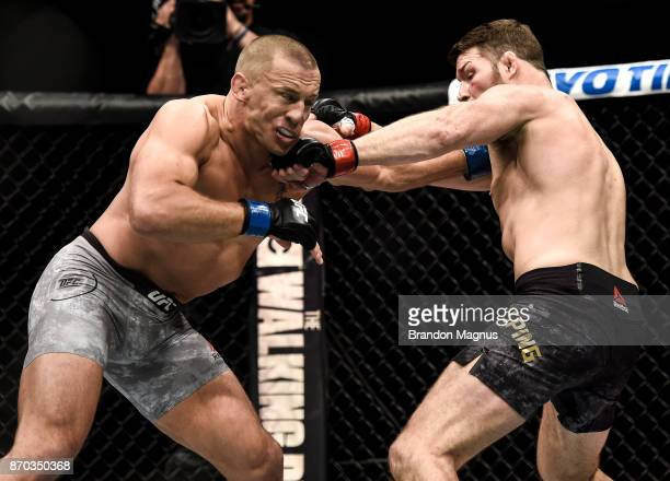 Michael Bisping of England punches Georges StPierre of Canada in their UFC middleweight championship bout during the UFC 217 event inside Madison...