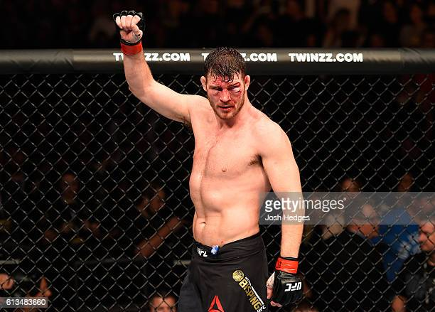 Michael Bisping of England raises his hand after facing Dan Henderson in their UFC middleweight championship bout during the UFC 204 Fight Night at...