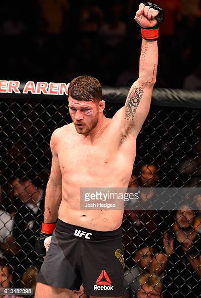 Michael Bisping of England raises his hand while facing Dan Henderson in their UFC middleweight championship bout during the UFC 204 Fight Night at...