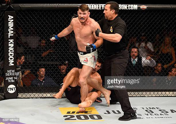 Michael Bisping of England wins in a first round knockout against Luke Rockhold in their UFC middleweight championship bout during the UFC 199 event...