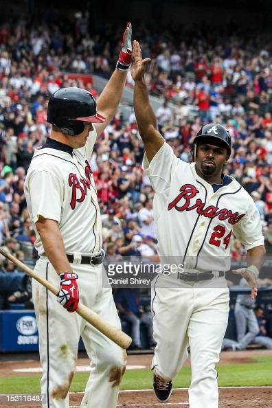 Michael Bourn celebrates with Chipper Jones of the Atlanta Braves after scoring in the fifth inning against the New York Mets at Turner Field on...
