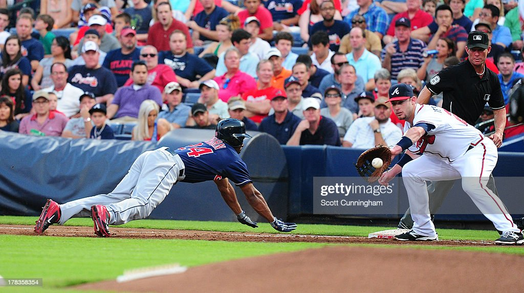 <a gi-track='captionPersonalityLinkClicked' href=/galleries/search?phrase=Michael+Bourn&family=editorial&specificpeople=835742 ng-click='$event.stopPropagation()'>Michael Bourn</a> #24 of the Cleveland Indians dives back safely to first base against Joey Terdoslavich #25 of the Atlanta Braves at Turner Field on August 29, 2013 in Atlanta, Georgia.