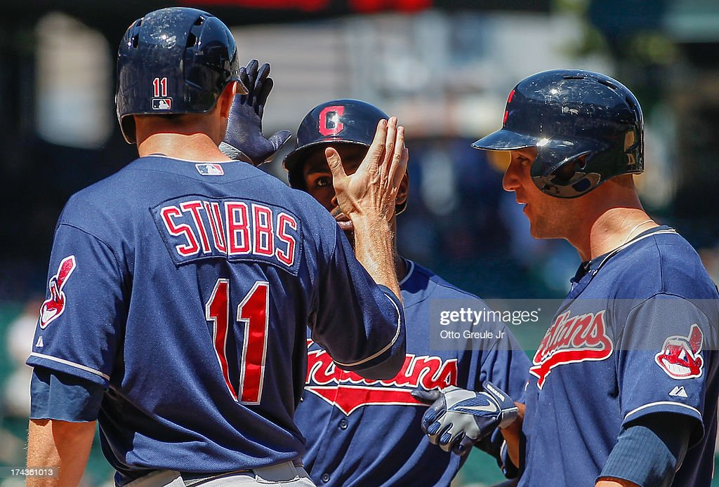 <a gi-track='captionPersonalityLinkClicked' href=/galleries/search?phrase=Michael+Bourn&family=editorial&specificpeople=835742 ng-click='$event.stopPropagation()'>Michael Bourn</a> #24 of the Cleveland Indians is congratulated by <a gi-track='captionPersonalityLinkClicked' href=/galleries/search?phrase=Drew+Stubbs+-+Baseball&family=editorial&specificpeople=4498334 ng-click='$event.stopPropagation()'>Drew Stubbs</a> #11 and <a gi-track='captionPersonalityLinkClicked' href=/galleries/search?phrase=Yan+Gomes&family=editorial&specificpeople=9004037 ng-click='$event.stopPropagation()'>Yan Gomes</a> #10 after hitting a grand slam in the fifth inning against the Seattle Mariners at Safeco Field on July 24, 2013 in Seattle, Washington.