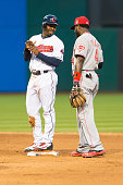 Michael Bourn of the Cleveland Indians talks to second baseman Brandon Phillips of the Cincinnati Reds between plays during the fourth inning at...