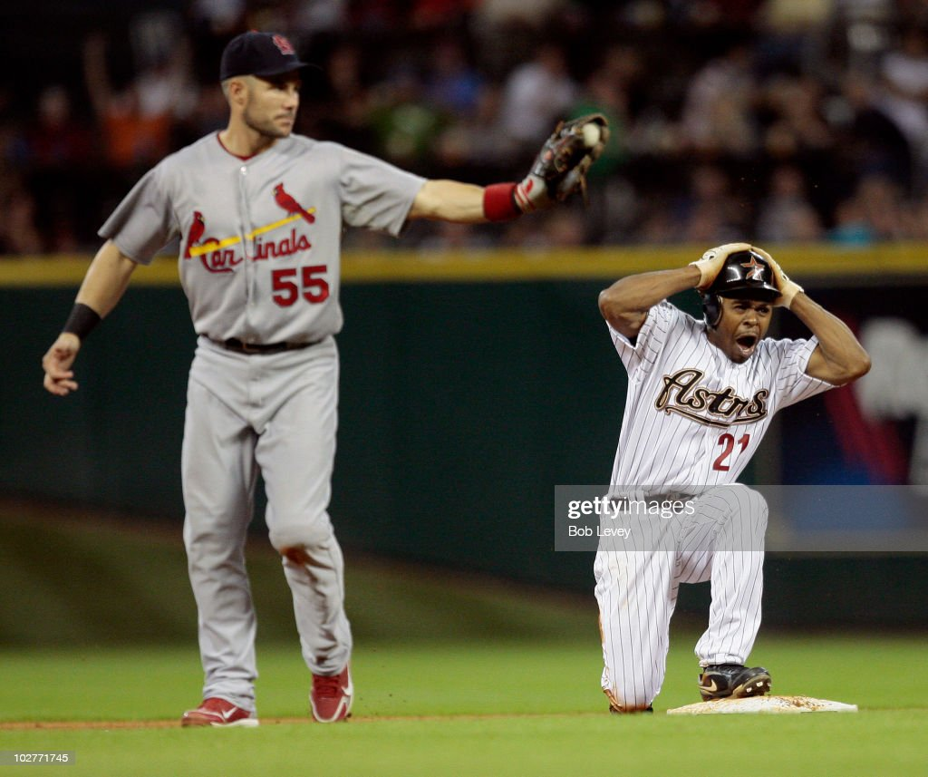 Michael Bourn of the Houston Astros reacts as second baseman Skip Schumaker of the St Louis Cardinals shows the ball to umpire Andy Fletcher who...