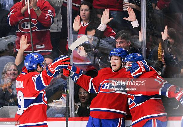 Michael Bournival Lars Eller and Brendan Gallagher of the Montreal Canadiens celebrate after scoring a goal in the second period against the...