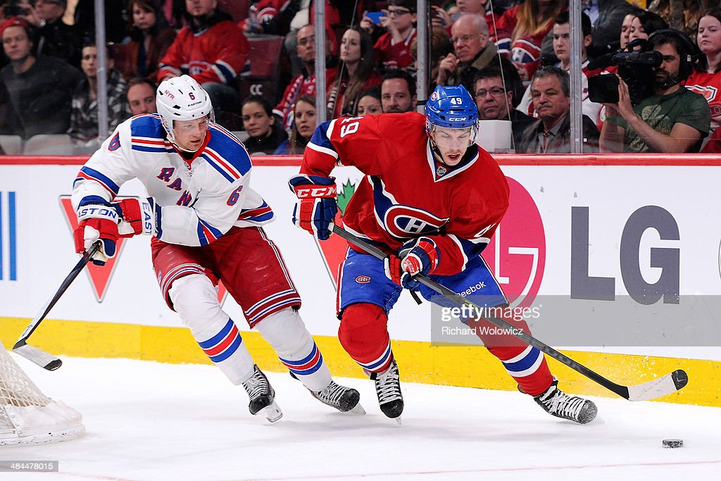Michael Bournival #49 of the Montreal Canadiens skates with the puck while being chased by Anton Stralman #6 of the New York Rangers during the NHL game at the Bell Centre on April 12, 2014 in Montreal, Quebec, Canada.