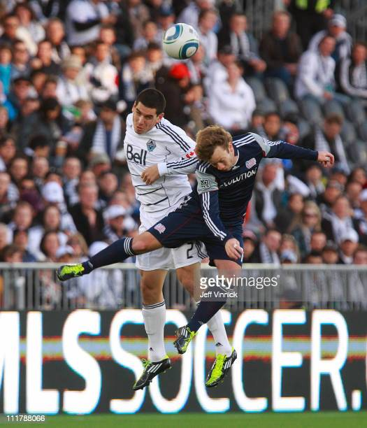 Michael Boxall of the Vancouver Whitecaps FC and Zack Schilawski of the New England Revolution head the ball during their MLS game April 6 2011 in...