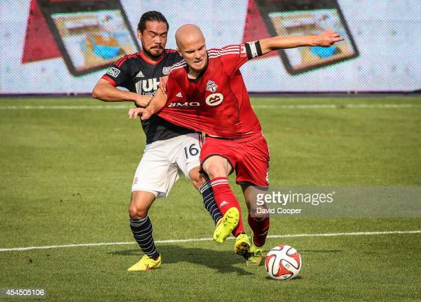 Michael Bradley of TFC has his jersey grabbed by Daigo Kobayashi of NER as the fight for possession during the game between Toronto FC and New...