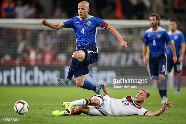 Michael Bradley of the USA is challenged by Christoph Kramer of Germany during the International Friendly match between Germany and USA at...