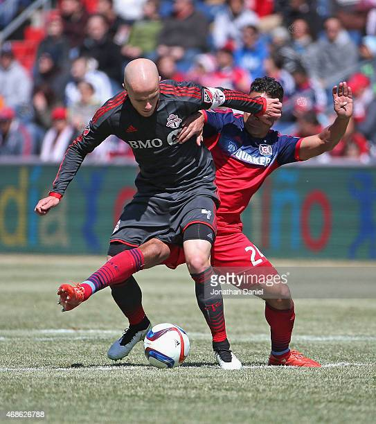 Michael Bradley of Toronto FC gets his hand in the face of Quincy Amarikwa of Chicago Fire as the battle for the ball during an MLS match at Toyota...