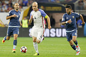 Michael Bradley of United States dribbles past Javier Mascherano and Augusto Fernandez of Argentina during the Semifinal match between United States...