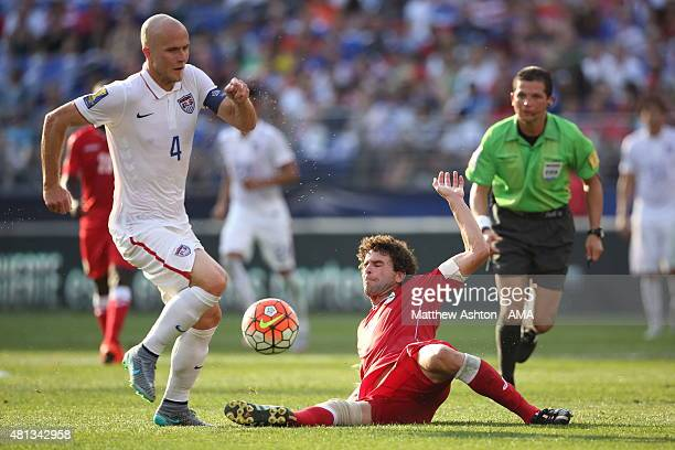 Michael Bradley of United States of America is tackled by Jorge Luis Clavelo of Cuba during the Gold Cup Quarter Final between USA and Cuba at MT...