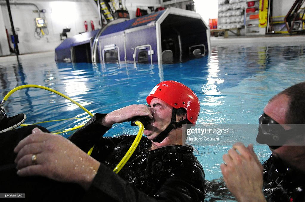 Michael Brady, left, a police officer in the Westchester County (NY) Police Department's aviation division, comes up to the surface with lots of water in his nose during an emergency breathing course at Survival Systems USA in Groton, Connecticut, October 5, 2011. The emergency breathing section of the course is part of the airplane ditching training that helps to train people how to escape from an airplane that has crash-landed in water.