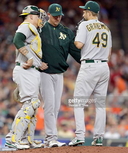 Michael Brady of the Oakland Athletics visits Kendall Graveman and Bruce Maxwell as the A's play against the Houston Astros in the fourth inning at...