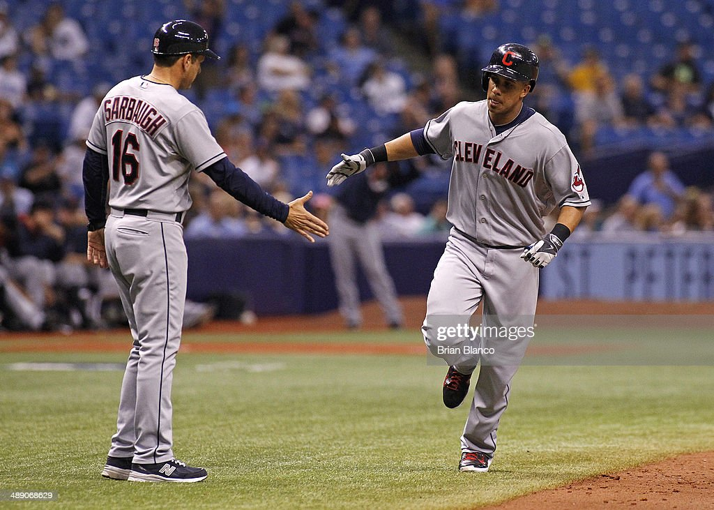 Michael Brantley (R) of the Cleveland Indians celebrates with third base coach Mike Sarbaugh #16 of the Cleveland Indians as he rounds the bases after hitting a solo home run during the seventh inning of a game against the Tampa Bay Rays on May 9, 2014 at Tropicana Field in St. Petersburg, Florida.