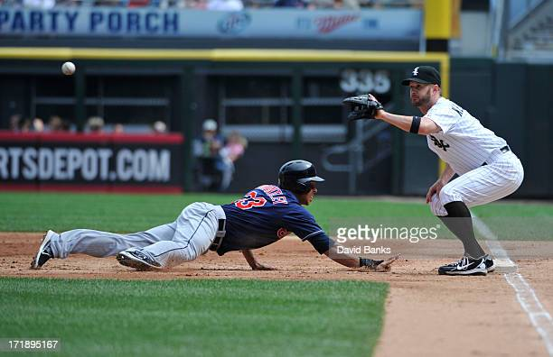 Michael Brantley of the Cleveland Indians dives back into first base as Jeff Keppinger of the Chicago White Sox takes the pickoff attempt during the...
