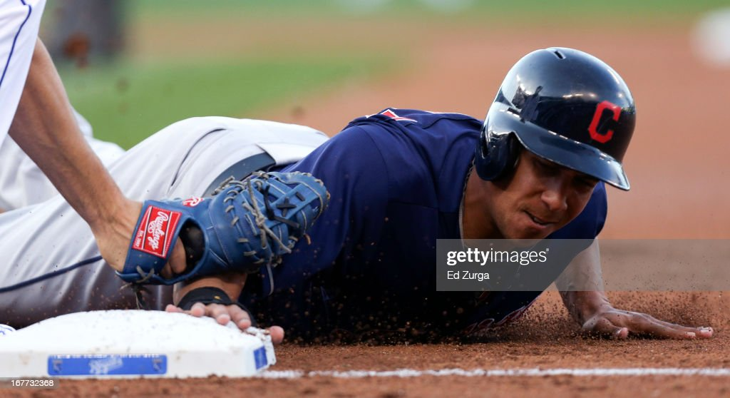 Michael Brantley #23 of the Cleveland Indians dives back safely to first as Eric Hosmer of the Kansas City Royals is late on the tag on a pick off attempt in the first inning during game two of a doubleheader at Kauffman Stadium on April 28, 2013 in Kansas City, Missouri.