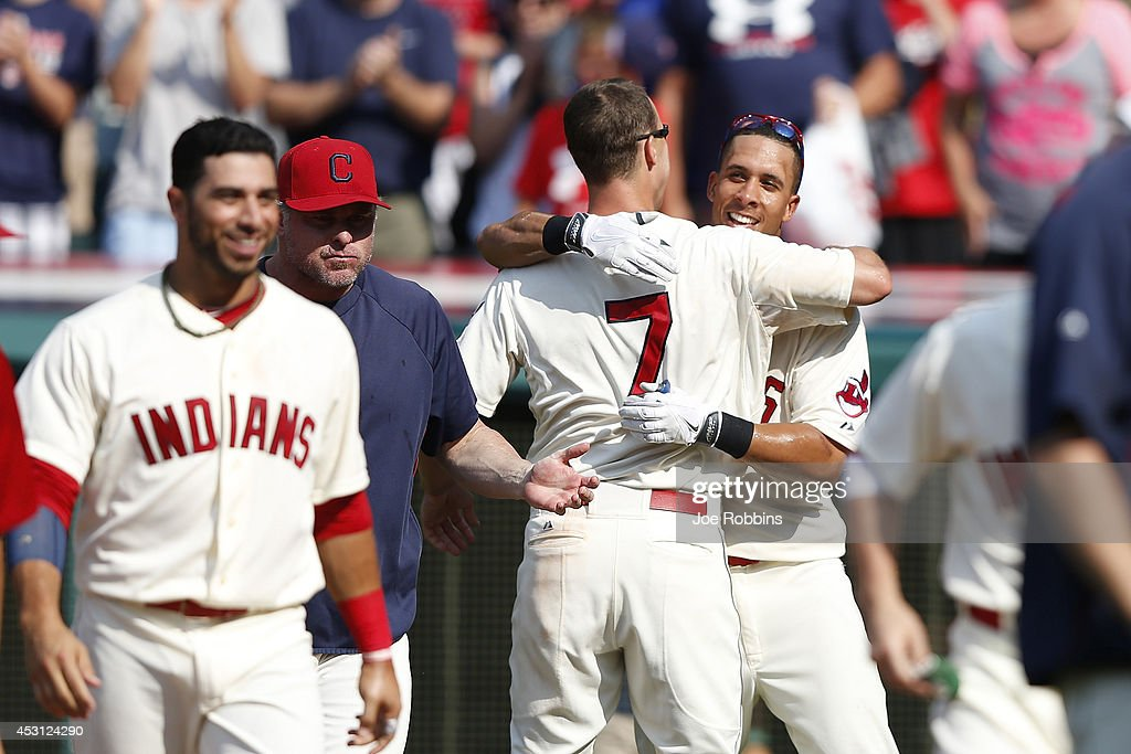 Michael Brantley #23 of the Cleveland Indians gets a hug from David Murphy #7 after hitting a home run to win the game in the 12th inning against the Texas Rangers at Progressive Field on August 3, 2014 in Cleveland, Ohio. The Indians won 4-3.