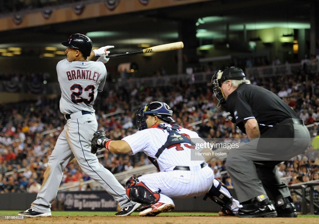 Michael Brantley #23 of the Cleveland Indians hits an RBI single as Josmil Pinto #43 of the Minnesota Twins catches during the sixth inning of the game on September 26, 2013 at Target Field in Minneapolis, Minnesota.