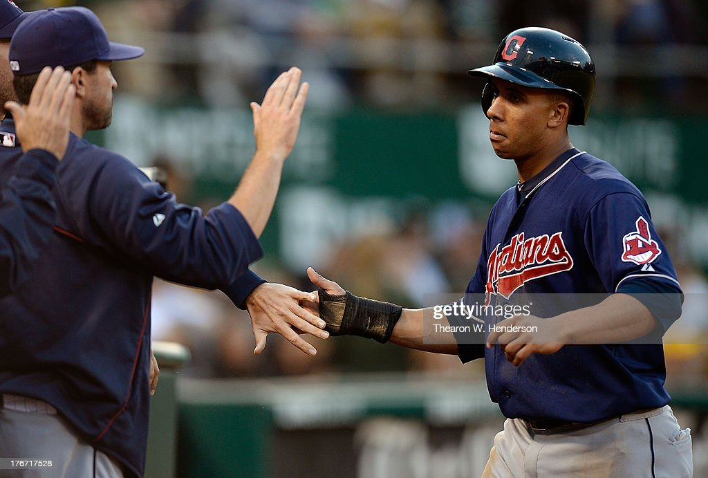 Michael Brantley #23 of the Cleveland Indians is congratulated by teammates after scoring on a Adrubal Cabrera RBI double in the six inning against the Oakland Athletics at O.co Coliseum on August 17, 2013 in Oakland, California.