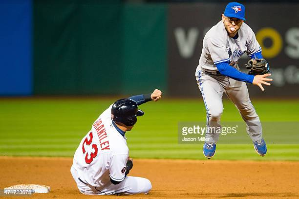 Michael Brantley of the Cleveland Indians is out at second as shortstop Jonathan Diaz of the Toronto Blue Jays throws to first on a ground ball hit...