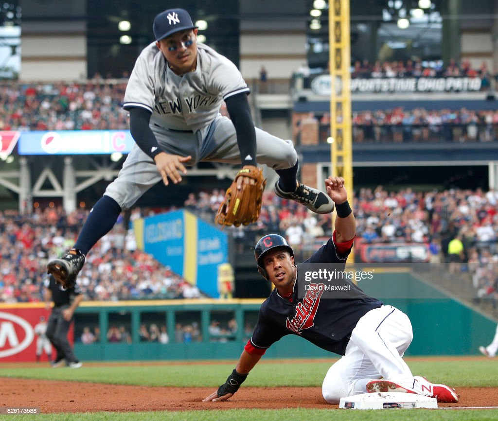 Michael Brantley #23 of the Cleveland Indians is safe at third as Ronald Torreyes #74 of the New York Yankees is unable to field the wild throw in the first inning at Progressive Field on August 3, 2017 in Cleveland, Ohio.