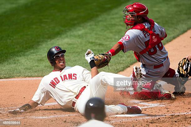 Michael Brantley of the Cleveland Indians slides in safe at home as catcher Carlos Perez of the Los Angeles Angels of Anaheim misses the tag during...