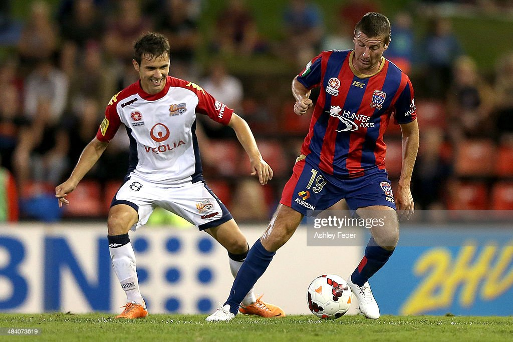 Michael Bridges of the Jets controls the ball ahead of Isaias of Adelaide United during the round 27 A-League match between the Newcastle Jets and Adelaide United at Hunter Stadium on April 11, 2014 in Newcastle, Australia.