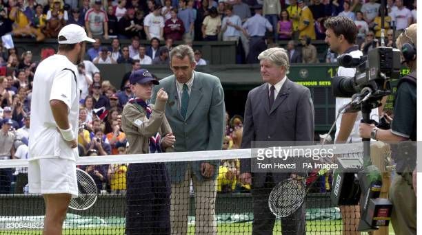Michael Brown aged 16 from The 133rd Bristol Special Needs Scout Group prepares to toss a coin to decide the first serve between Goran Ivanisevic of...