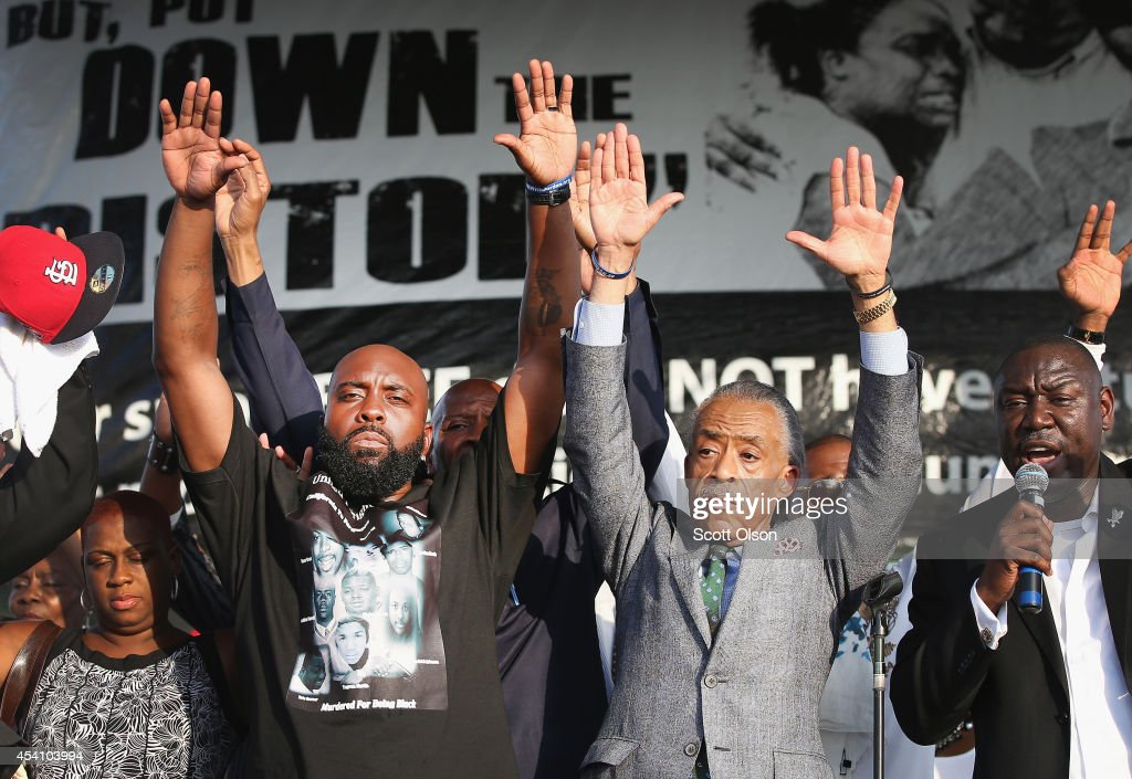 Michael Brown Sr. (L) and Civil rights leader Rev. Al Sharpton (2nd from left) hold up their hands as attorny Benjamin Crump (R) speaks at Peace Fest music festival in Forest Park on August 24, 2014 in St. Louis, Missouri. Brown is the father of Michael Brown who was shot and killed by a police officer in nearby Ferguson, Missouri on August 9. Michael will be buried tomorrow.