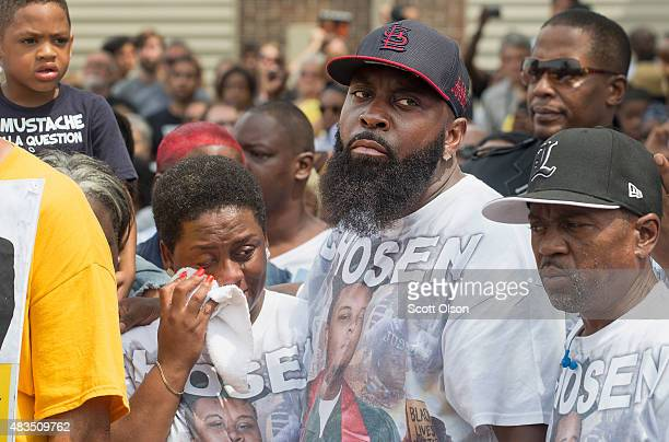 Michael Brown Sr comforts his wife Cal Brown during a moment of silence in the center of Canfield Street where Michael Brown Jr was killed during a...