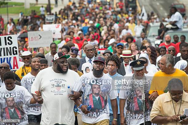 Michael Brown Sr leads a march from the location where his son Michael Brown Jr was shot and killed following a memorial service marking the...
