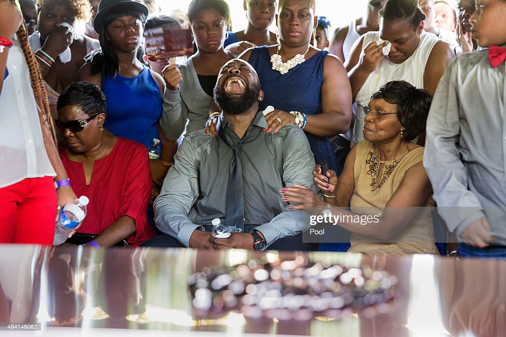 Michael Brown Sr yells out as the casket is lowered into the ground during the funeral for his son Michael Brown at St Peters Cemetery on August 25...