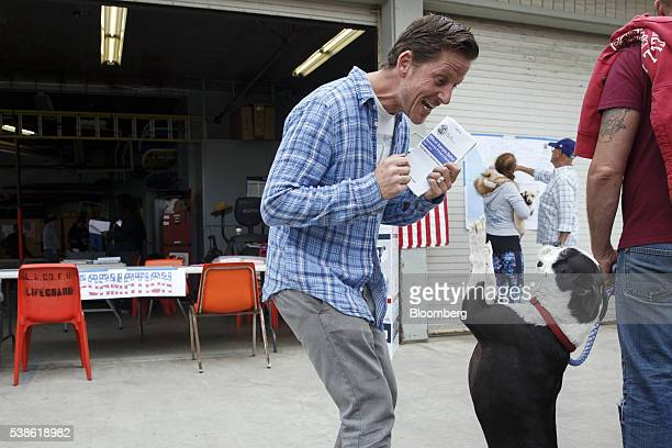 Michael Brunt is greeted by his dog Tonka after voting during the presidential primary election at the Venice Beach Lifeguard polling station in Los...